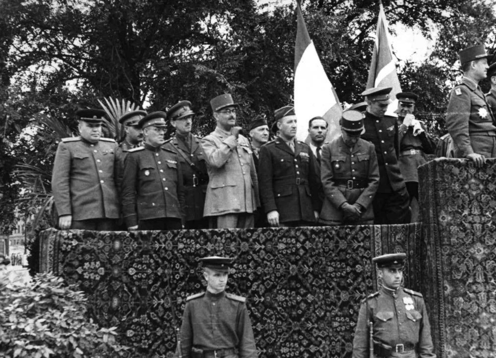 """Bei dieser großen Zeremonie am Schwarzenbergplatz sollte der Beginn der gemeinsamen Verwaltung Wiens durch alle vier alliierten Mächte markiert werden. Sie betont bewusst die Zusammenarbeit in Zeiten des beginnenden """"Kalten Kriegs""""."""