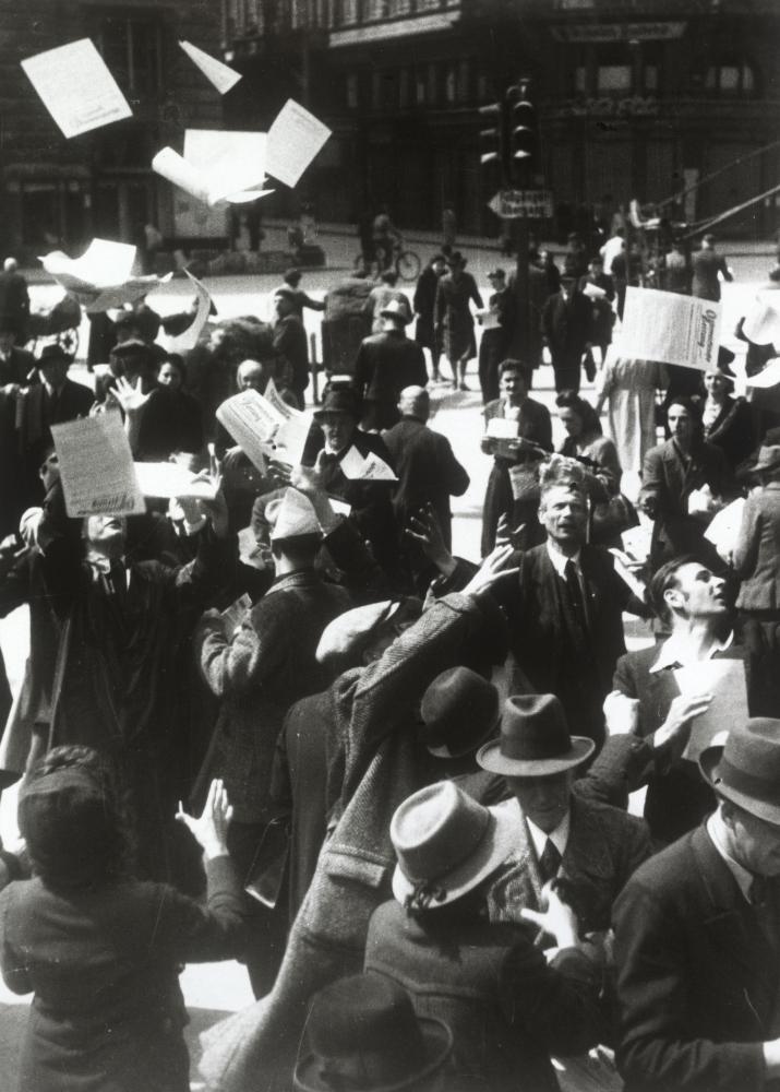 """Noch während die Kämpfe um Wien tobten, bereitete die sowjetischen Armee bereits die """"Österreichische Zeitung"""" vor. Der Fotograf inszeniert hier die Reaktion der Menschen auf die Verteilung dieser ersten Zeitung nach der NS-Herrschaft."""