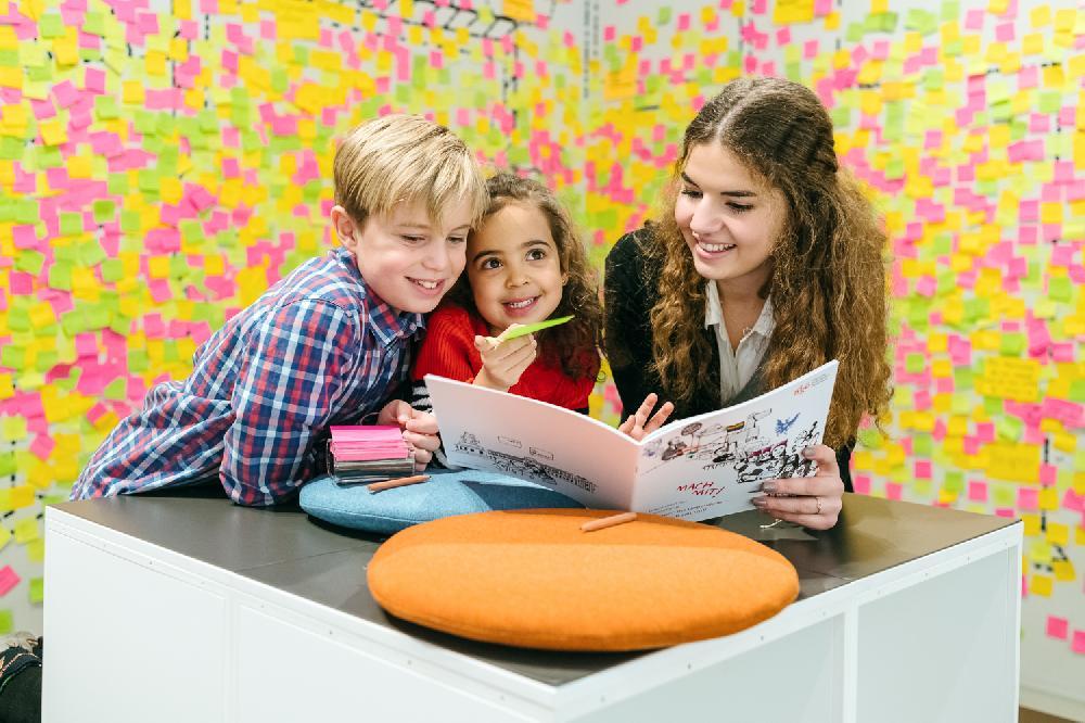 Am Fotos sind drei Kinder zu sehen, die gemeinsam ein Heft anschauen.